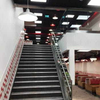 Glass balustrade with stainless steel handrails located in a high end restaurant chain