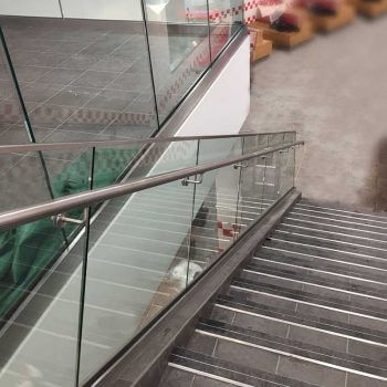 Glass balustrade and stainless steel handrails leading down staircase in retail outlet