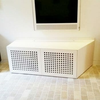 Perforated steel audio visual unit finished in white, in situ
